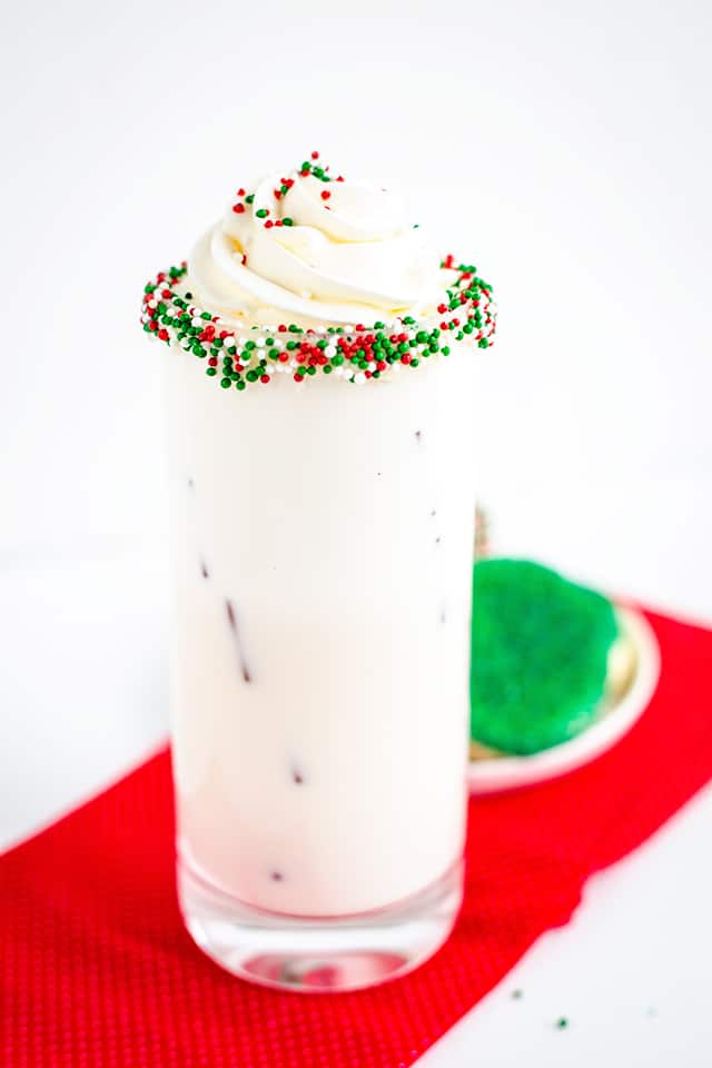 A sugar cookie cocktail sits on top of a red cloth next to a plate of green cookies. The drink is white and creamy, with whipped cream swirled on top. It is garnished with red, white and green sprinkles.
