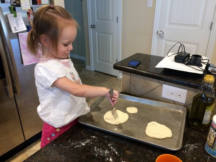 Eliza helped mommy make pizza. She loved poking the crust.