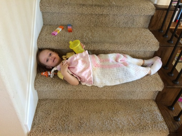 "Eliza ""sleeping"" on the stairs with her water, her fish, her blanket and her tower"