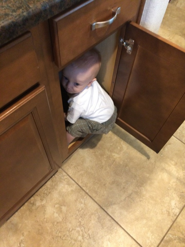 James is trying to hide in the cupboard.