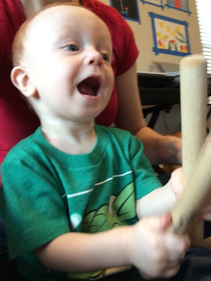 James playing the sticks at music class.