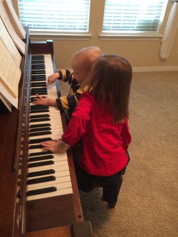 James playing the black keys on the piano. He focuses really intently on this.