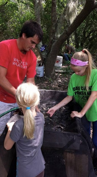 Scott Dawson in the field showing his daughters how to do archaeology.