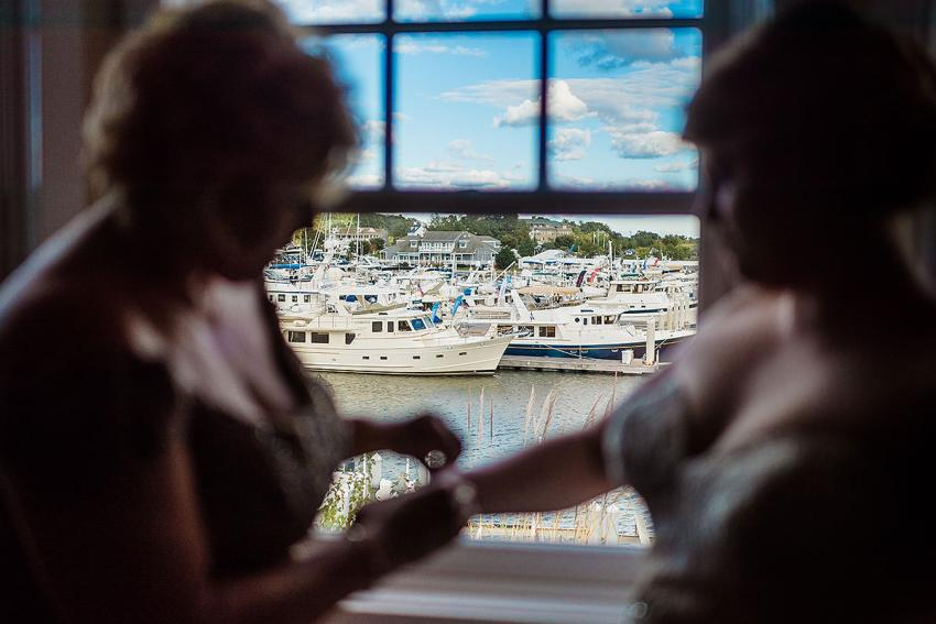 mother and bride getting ready in front of harbor at Chesapeake bay beach club wedding by Washington DC Wedding Photographer Adam Mason
