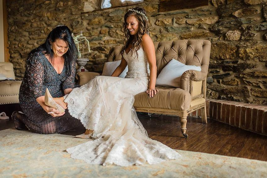 mother helping daughter the bride put on her shoes at wyndridge farm wedding photos by Washington DC Wedding Photographer Adam Mason
