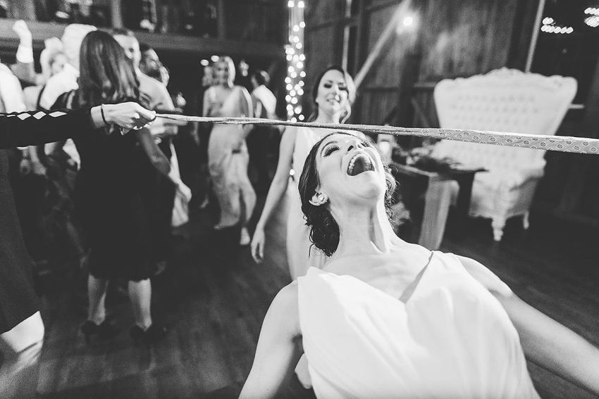 bridesmaids doing limbo at wyndridge farm wedding by Washington DC Wedding Photographer Adam Mason