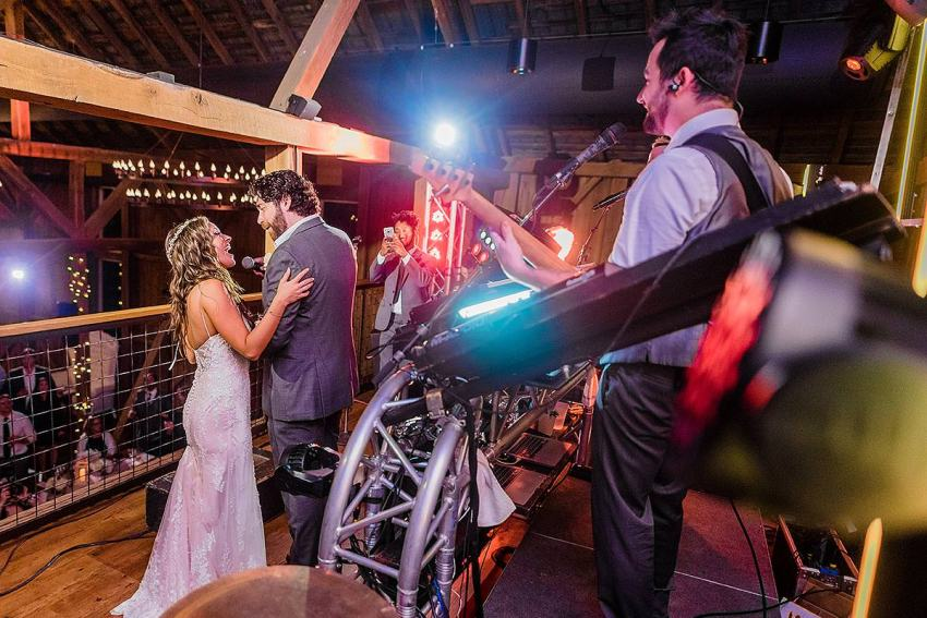 bride and groom singing along rock wedding band go go gadget at wyndridge farm wedding