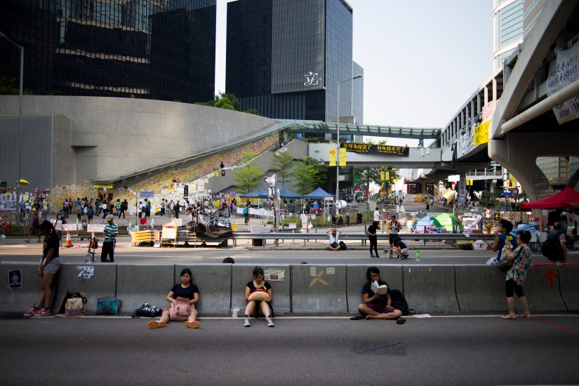 """Students read, do their homework, or rest, on Harcourt Road in Hong Kong on October 7, 2014. This usually busy four-lane highway has served as town square to thousands of Hong Kong residents during the #OccupyCentral protests. In the background, the every expanding """"Lennon Wall"""" features messages of support written on bright post-it notes. (Photo: Adam McCauley)"""