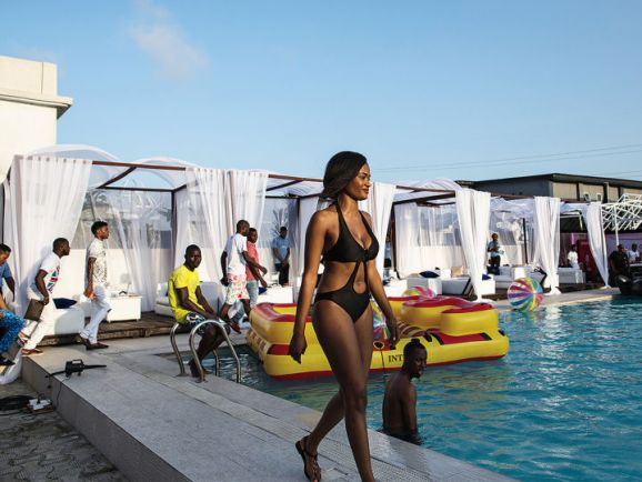 A woman walks by the pool at a party hosted by Quilox and promoted by Bizzle.
