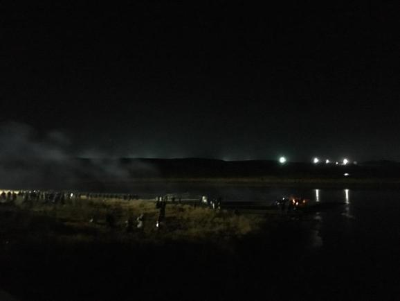 Police on left; water protectors huddled around fires for warmth; DAPL lights on right