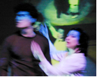 MARY and the CREATURE are both on stage. Their images appear recursively in the monitors, and their speaking is overlaid with computerized VOICEs.