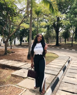 Adaora wearing side split trousers slogan tee