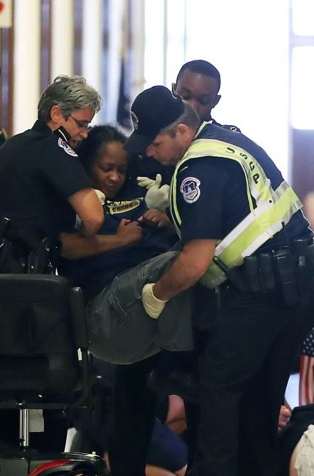 Being lifted by three police officers as she is being arrested