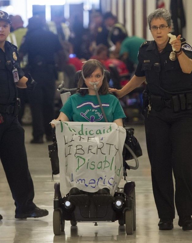 """In her wheelchair with a sign that reads 'Medicaid is Life and Liberty for Disabled Americans"""" surrounded by police officers"""