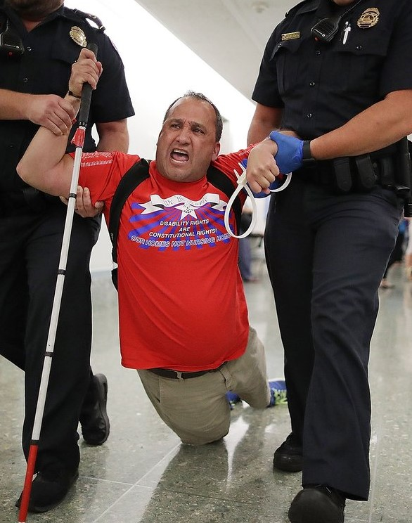 Being dragged by two police officers with his white cane in hand