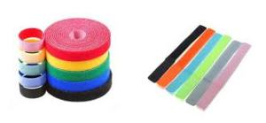 On the left of the picture there is a stack of coiled velcro cable ties in a variety of colours. On the right are some of these cable ties lined up in a row.
