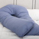 A dark blue pregnancy pillow on a bed