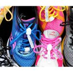 Four trainers in a row, yellow, blue, pink, black. Each one is laced with a corresponding coloured pair of laces. Where the knot of a bow on laces would be, there is instead a small white clasp.