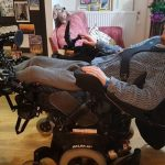 Me, stretched out in my wheelchair. My feet are on the leg-rests on the left of the image an d my head is towards the top at the right. You can see me being strapped in using a 4 point harness, with my arms resting on channel armrests.