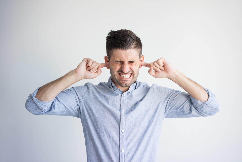 hombre tapándose los oídos aislamiento acústico insonorización