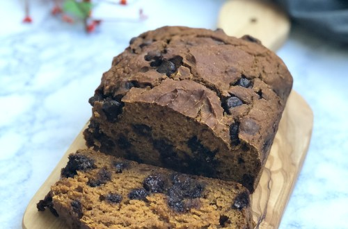 Pumpkin Chocolate Chip Bread on a serving board with a gray towl