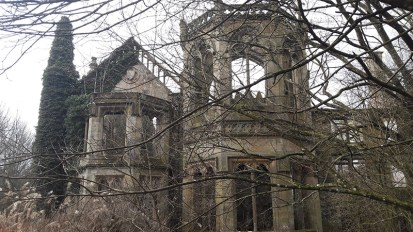 Image of east front of Crawford Priory ruins, part-covered with ivy and with trees in foreground