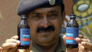 government official displays seized cough syrup