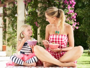 Mother And Daughter Enjoying Breakfast Cereal Outdoors Together