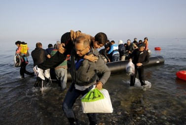 Syrian refugees on an overcrowded dingy land on Kos after crossing part of the Aegean Sea from Turkey to Greece