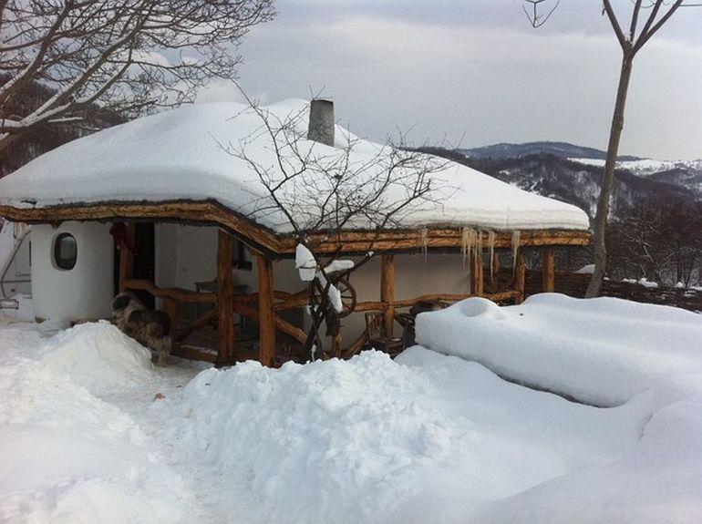 Casa mica cu acoperis din pamant si iarba pe timpul iernii