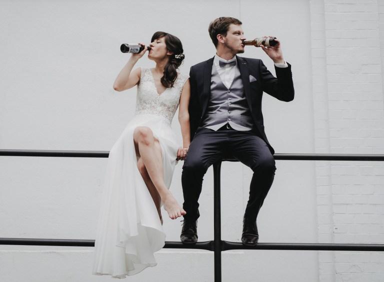 Ein Brautpaar sitzt barfuss vor einem Tangostudio in Hamburg und trinkt selbstgebrautes Craft Beer