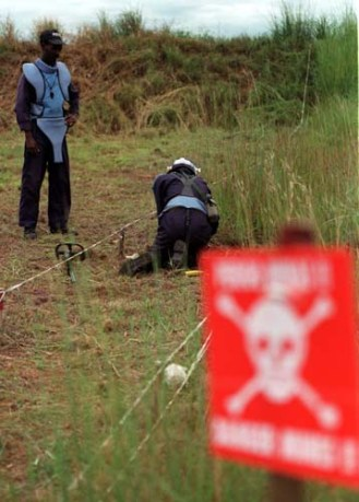 A mine clearance supervisor stands over his colleague as he goes about the task of searching for land mines around the airport in the central Angolan town of Huambo, Tuesday February 17, 1998. Over 20 000 mines have been laid in a 10km stretch around the airport.(AP Photo/Adil Bradlow)