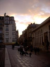 People gather outside as the sun sets outside of the Musée d'Orsay.