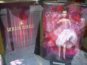An official Moulin-Rouge-themed Barbie sits in a shop window. Barbie is everywhere and in every profession, including topless dancing.