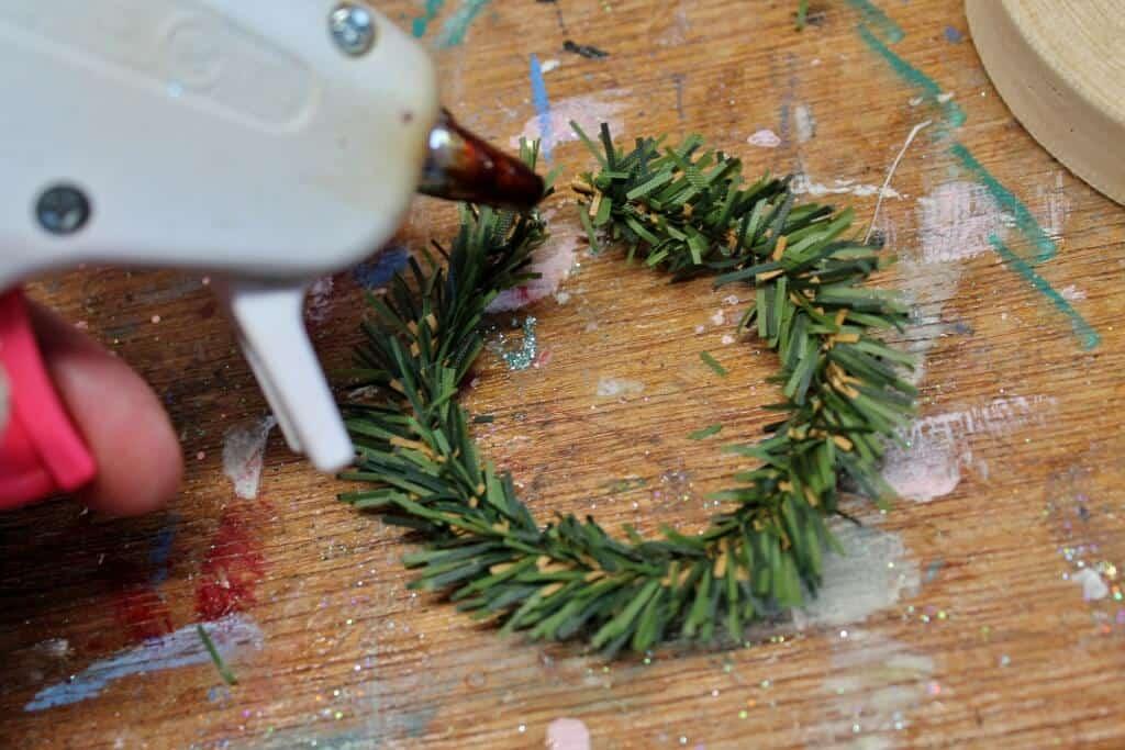 gluing-green-garland-to-make-wreath-1024x683