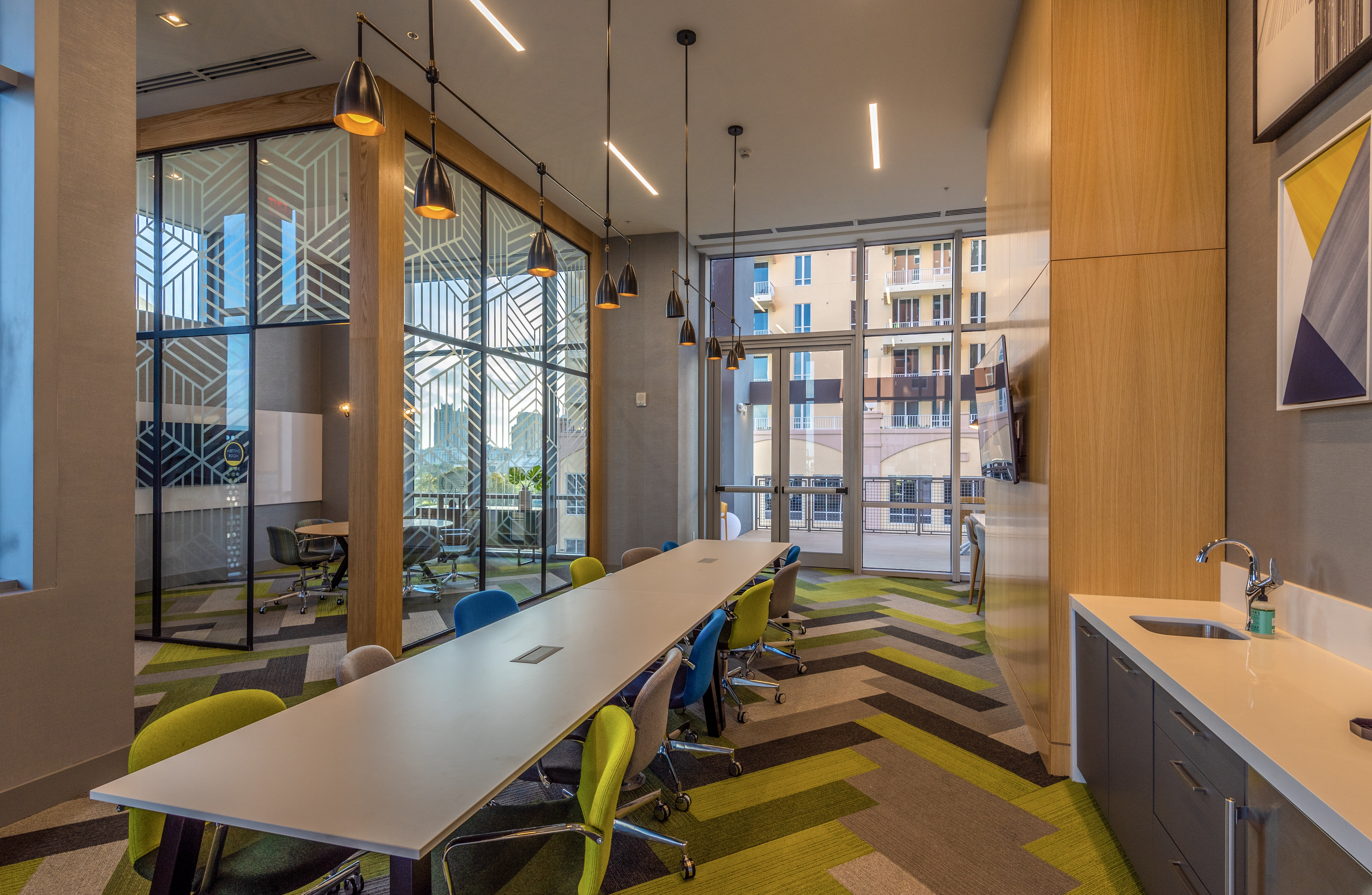 Modern apartment common meeting space with long conference table, chairs, a sink, and separate private office room with glass walls.