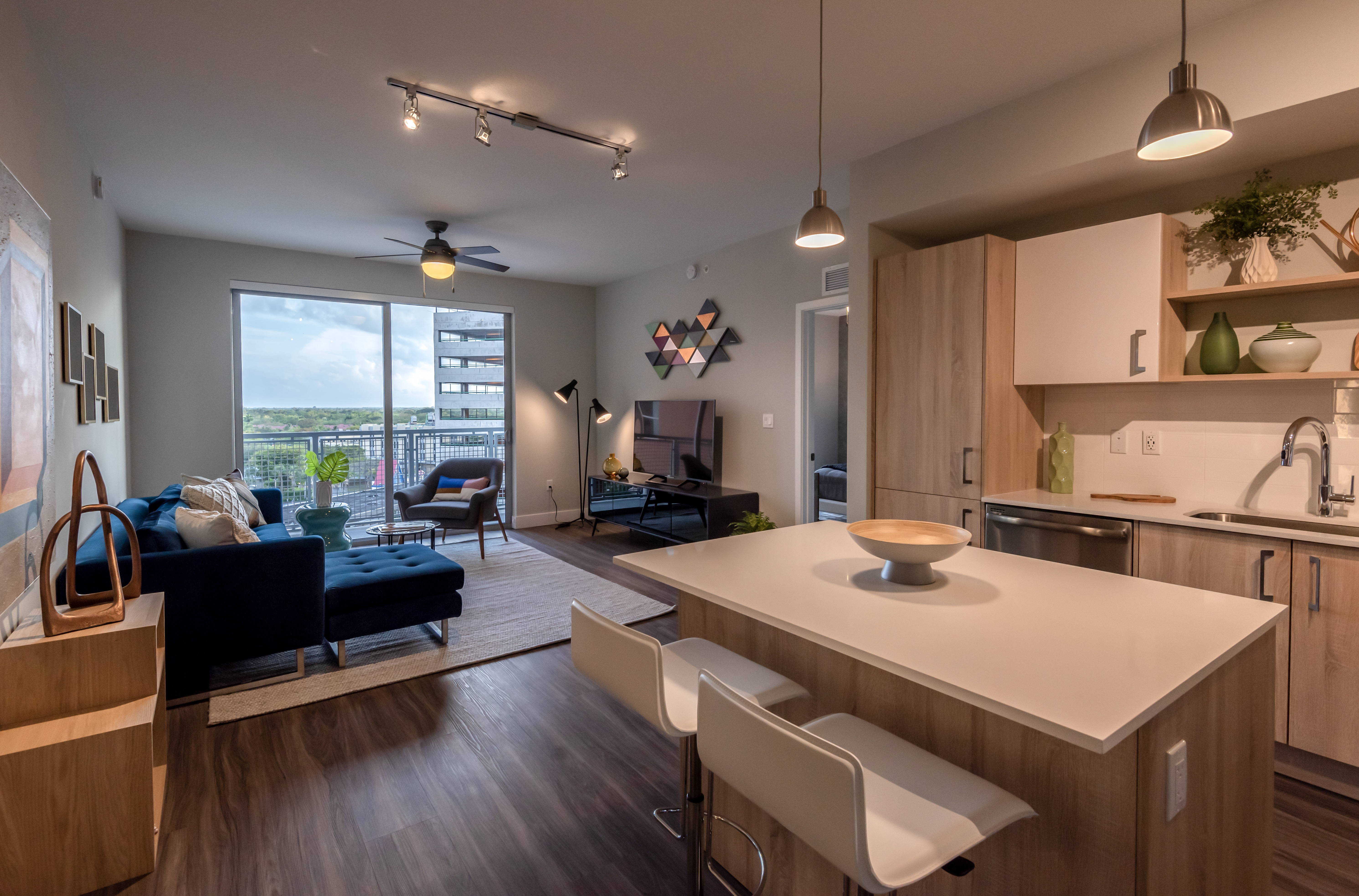 Furnished modern apartment with light wood kitchen cabinets, living room view with balcony