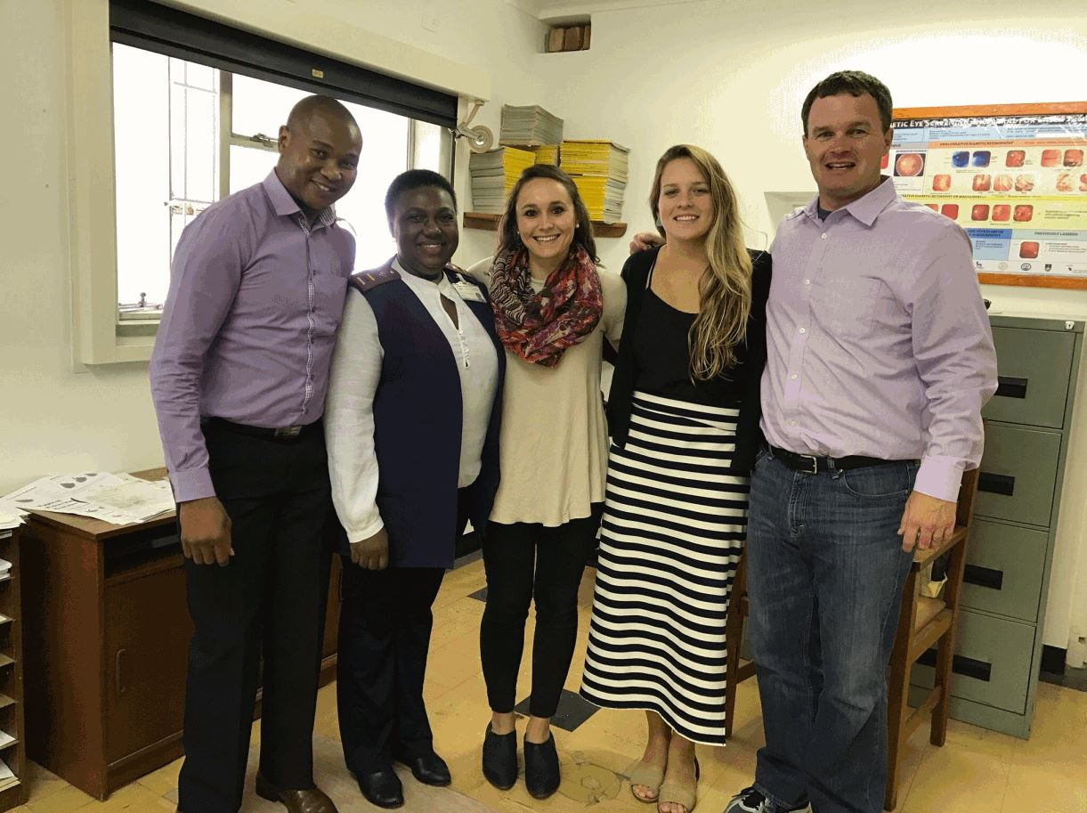 Sierra poses with a group of four other people on a visit to a women's health facility to South Africa.]