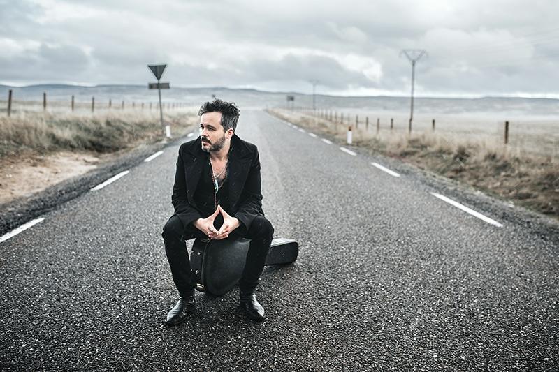 Twanguero sentado en el camino en su guitarra