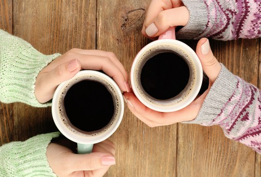Two women in jumpers holding a cup of black coffee each in mugs