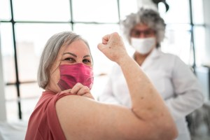Image: Woman being vaccinated and flexing biceps muscle - wearing face mask