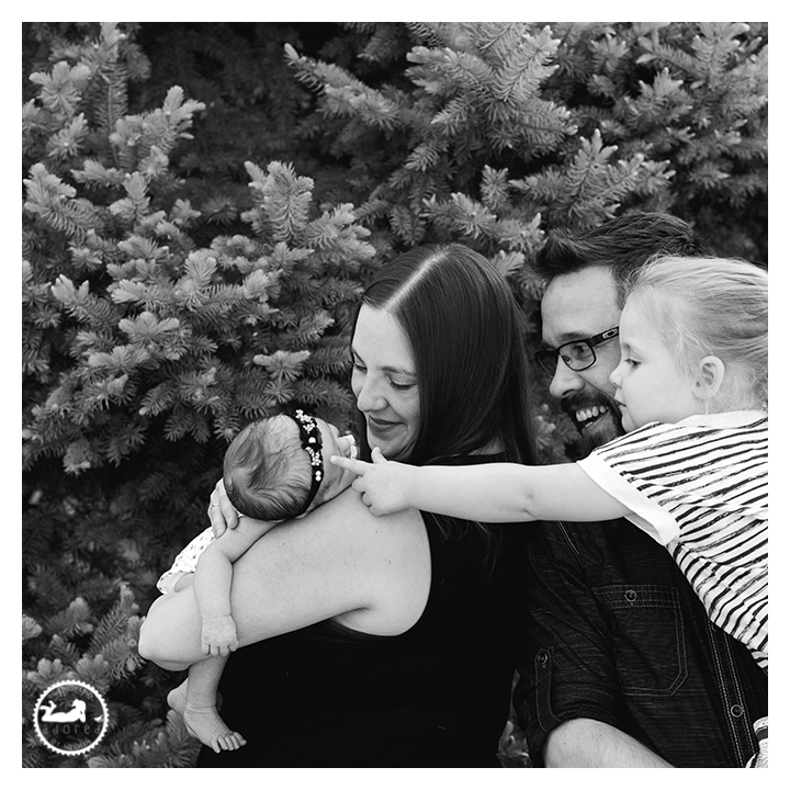 Black and white portrait of family with new baby sister