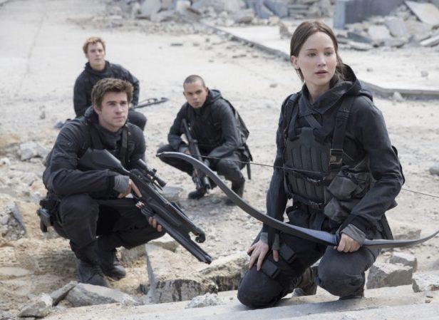 Szenenbild aus HUNGER GAMES: MOCKINGJAY - Rebellen auf dem Weg ins Kapitol: Katniss (Jennifer Lawrence), Gale (Liam Hemsworth), Finnick (Sam Claflin) und Messalla (Evan Ross) - © 2015 StudioCanal