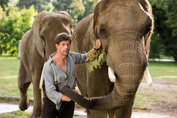 Filmstill aus DIE FRAU DES ZOODIREKTORS (2017), Johan Heldenbergh mit zwei Elefanten - © Universal Pictures Germany