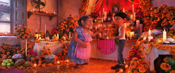 "COCO - In Disney•Pixar's ""Coco,"" Abuelita (voice of Renée Victor) and Miguel (voice of Anthony Gonzalez) ensure that their home is adorned for Día de Muertos, including an elaborate ofrenda that holds several framed family pictures, flowers, candles, favorite foods and—because they are in the shoemaking business—shoes. ""Coco"" opens in n U.S. theaters on Nov. 22, 2017. ©2017 Disney•Pixar. All Rights Reserved."
