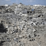 Palestinians walk across the rubble of destroyed buildings and homes in the Shejaiya residential district.