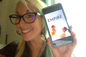 Woman showing her Empire Book on iphone
