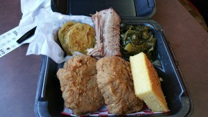 Salmon croquette with fried green tomatoes, a slice of beef brisket, collard greens and cornbread.