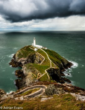 South Stack lighthouse is built on Ynys Lawd, a small rocky island just off the edge of Holy Island, which itself is an island just barely separate from the main part of Anglesey, north Wales, UK. To reach it you need to descend a switchback stairway running down the cliff face, over 400 steps down and 400 back up. At the bottom a bridge carries the visitor over a chasm to the island. A height of 41 metres the South Stack Lighthouse has warned passing ships of the treacherous rocks below since its completion in 1809.