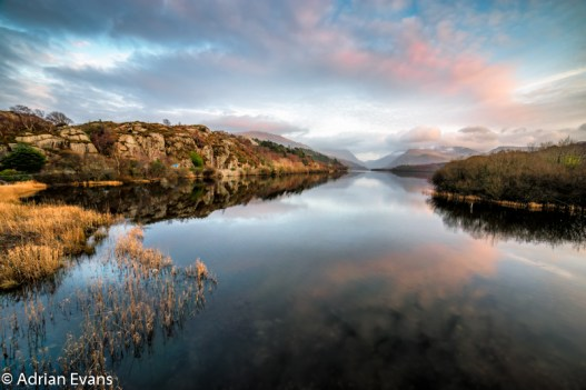 Padarn lake late evening awaiting sunset, looking towards Dolbadarn Castle and beyond to Snowdon north Wales, UK